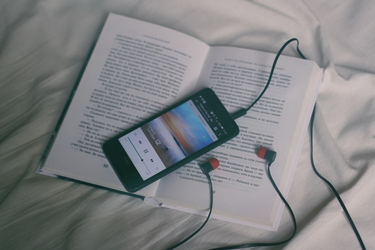 phone, headphones, and book on bed - get a good night's sleep