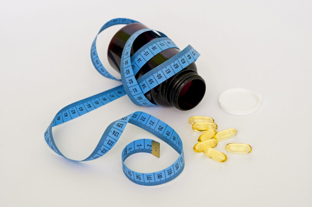 new years diet fads bottle of vitamins and measuring tape