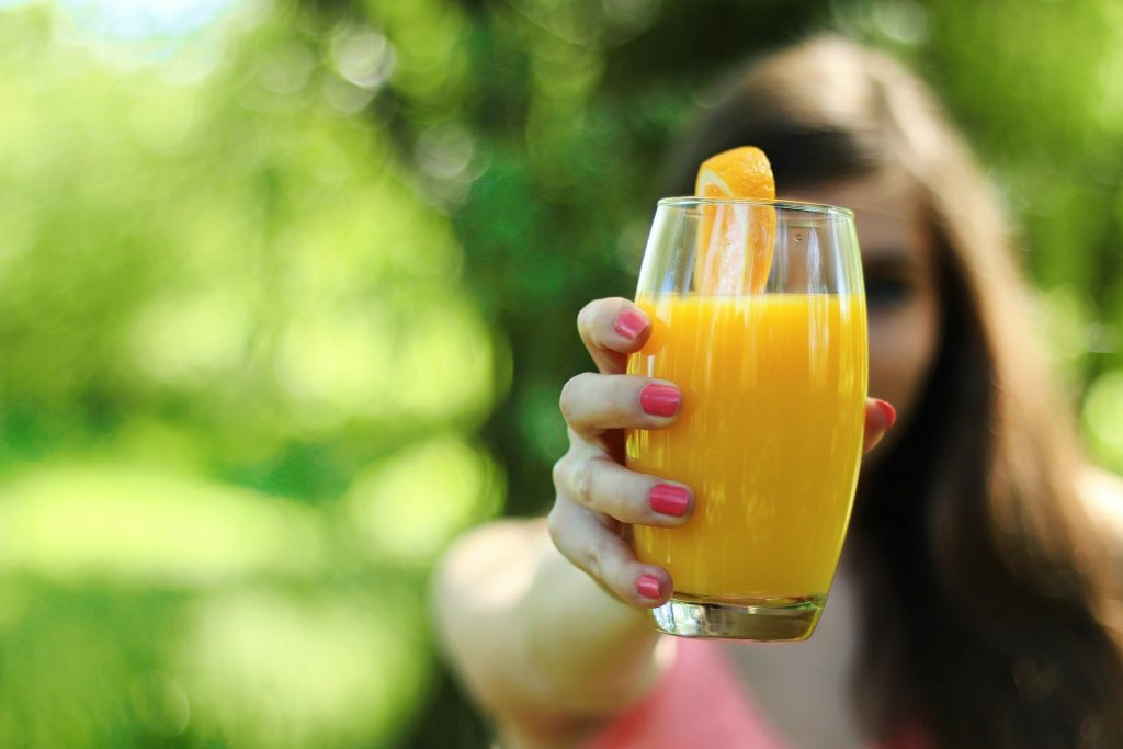 a woman holding a glass of orange juice - mood-boosting superfoods